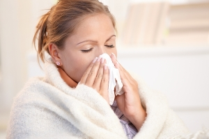 Young woman having flu blowing her nose