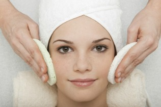 Young woman receiving face cleansing at beauty spa